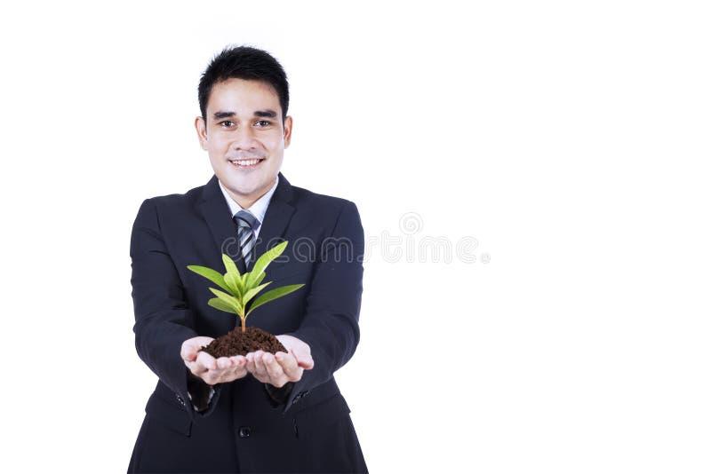 Isolerad affärsman som rymmer en växt fotografering för bildbyråer