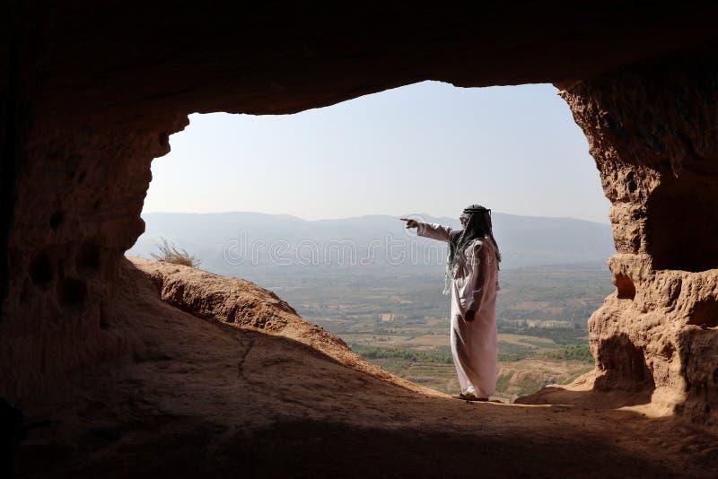 ISOLERAD ARABISK MAN I EN AVLÄGSEN GROTTA MED DJELLABA OCH DEN ARABISKA HALSDUKEN SOM UT PEKAR royaltyfri fotografi