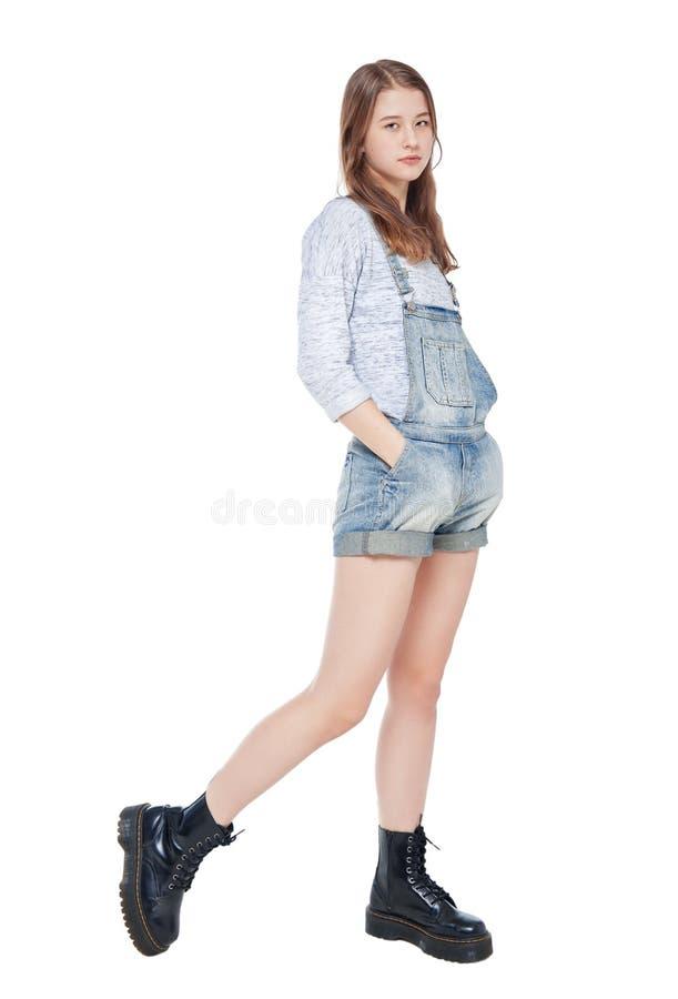 Isolerad barnmodeflicka, i att posera för jeansoveraller royaltyfria bilder