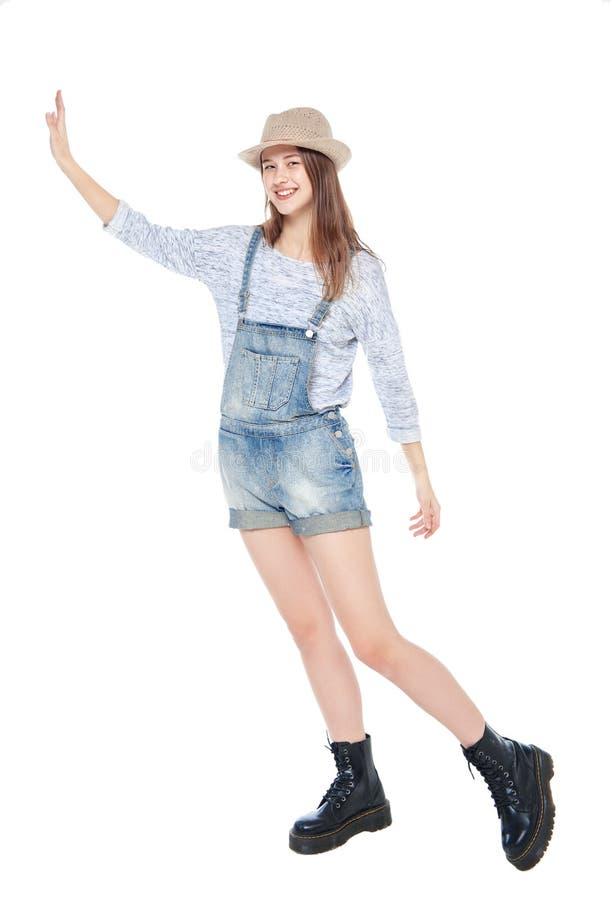 Isolerad barnmodeflicka i jeansoveraller som skjuter något royaltyfria bilder