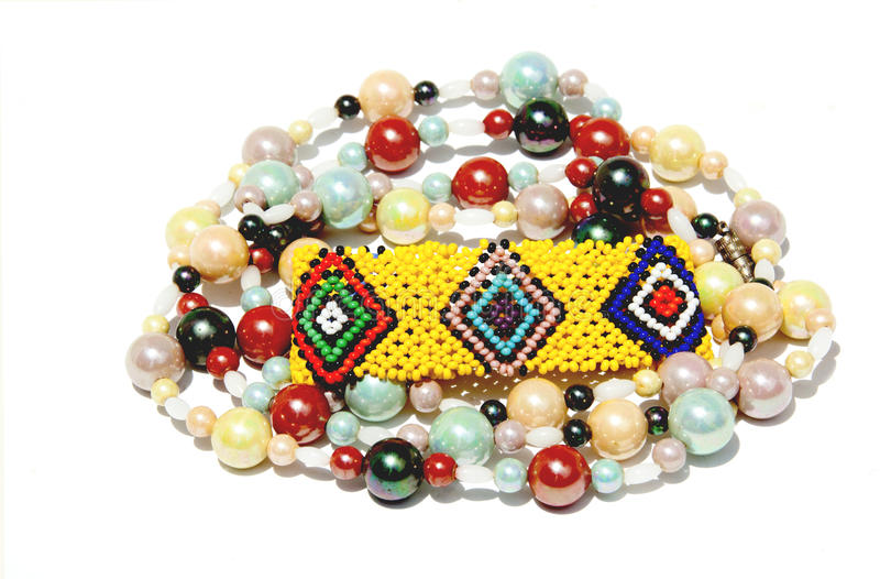 Isolerad färgrik prydd med pärlor armband och halsband på vit arkivfoto
