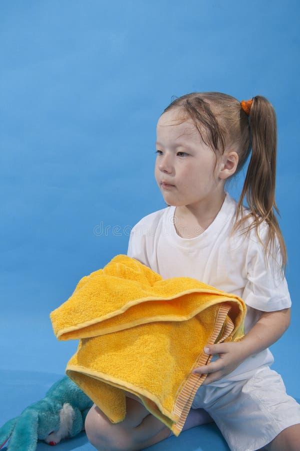 isolerad flicka hålla liten handdukyellow royaltyfria foton