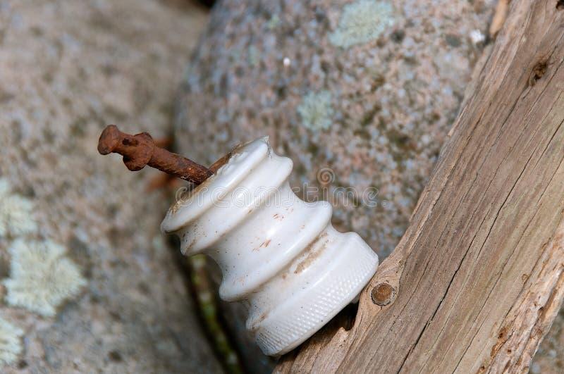 Isolerad gammal vit exponeringsglasisolator på en cederträstaketstolpe arkivbild