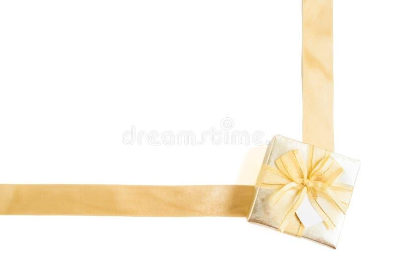 Isolerad guld- gåvaask med det guld- bandet royaltyfri foto