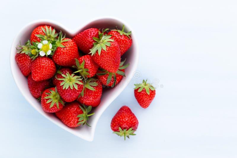 isolerad jordgubbewhite f?r bakgrund hj?rta Nya jordgubbar i platta p? den vita tr?tabellen B?sta sikt, kopieringsutrymme fotografering för bildbyråer