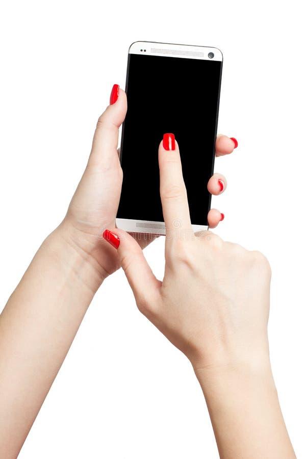 Isolerad kvinnlig hand som rymmer en telefon med den svarta skärmen på vit bakgrund arkivfoto