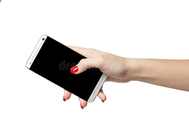 Isolerad kvinnlig hand som rymmer en telefon med den svarta skärmen på vit bakgrund royaltyfria foton