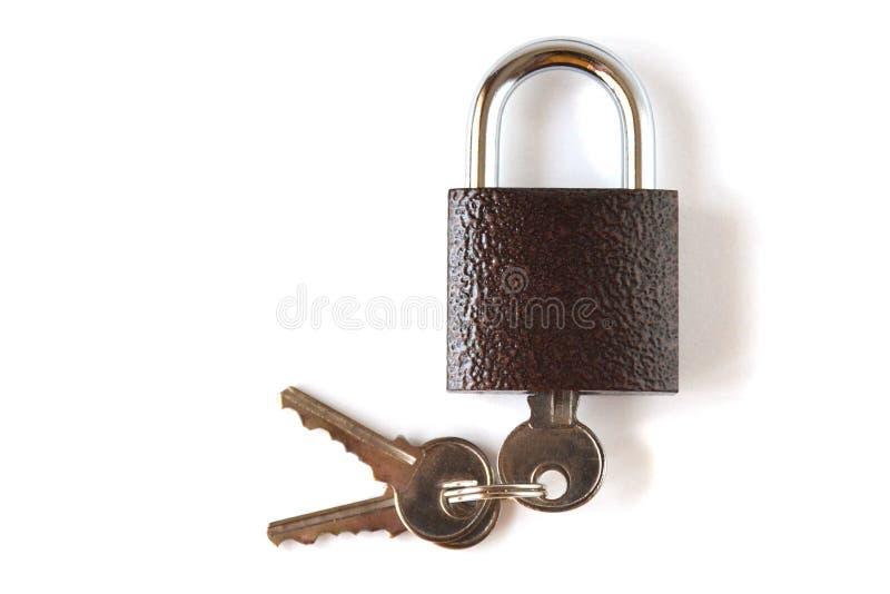 Isolerad låst textural brun hänglås med en grupp av tre tangenter på en vit bakgrund royaltyfri foto