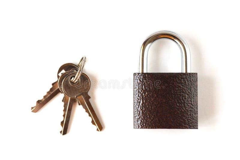 Isolerad låst textural brun hänglås med en grupp av tre tangenter på en vit bakgrund fotografering för bildbyråer