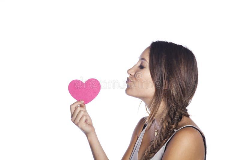 Isolerad lycklig ung caucasian kvinna som rymmer en hjärta och ger en kyss royaltyfria foton