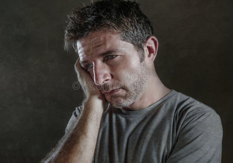 Isolerad mörk bakgrundsstående av 30-tal till den ledsna 40-tal och den deprimerade mannen som ser fundersamt och bekymrat lidand royaltyfria foton
