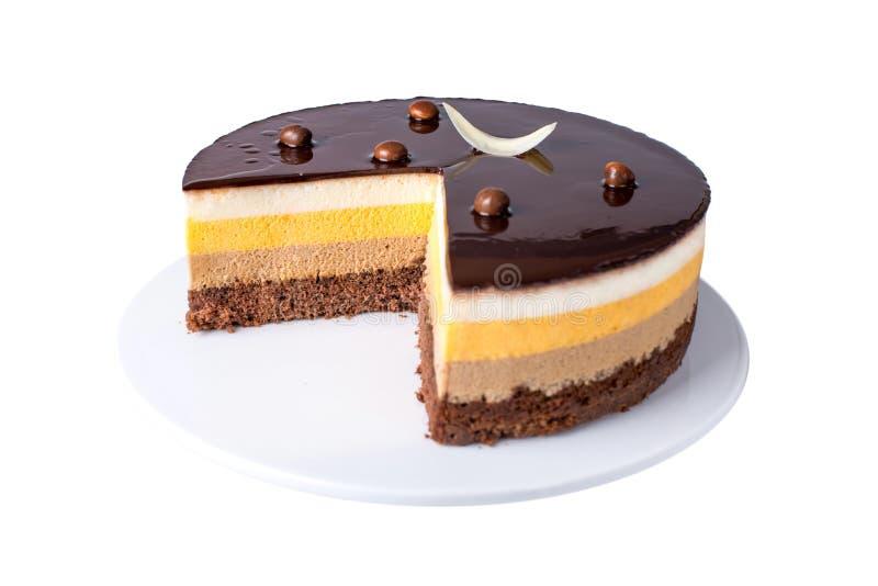 Isolerad orange chokladkaka med lager av delikat souffle, en läcker hemlagad efterrätt royaltyfria foton