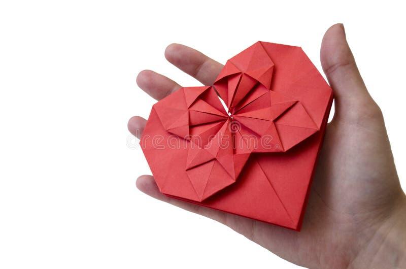 Isolerad röd pappers- hjärta gjorde i origamiteknik i kvinnlig hand på en vit bakgrund Begrepp av förälskelse, omsorg, hälsa, liv royaltyfri bild