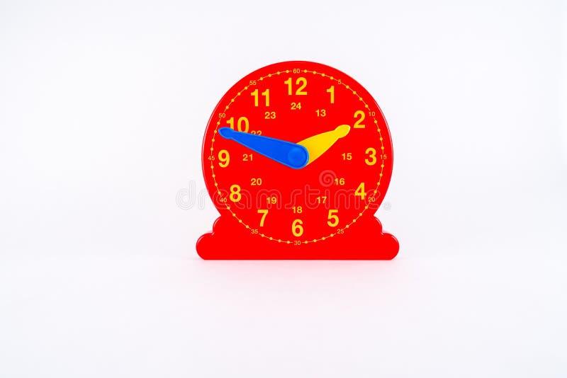 Isolerad röd plast- klockaleksak för lärande tid arkivfoto