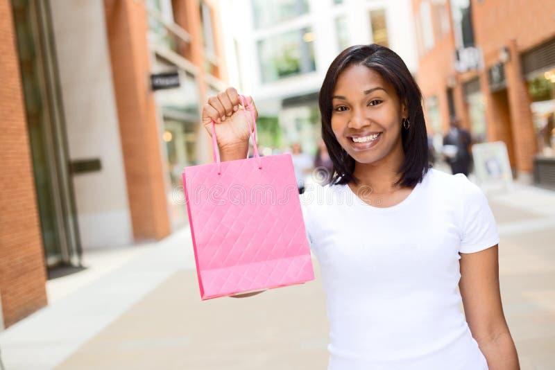 isolerad shoppa vit kvinna för bakgrundspåse holding arkivbild
