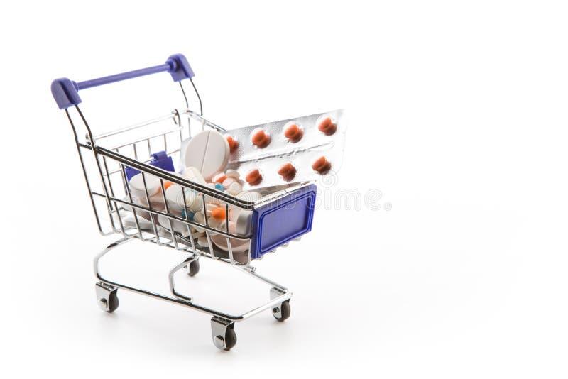 Isolerad shoppingvagn mycket med preventivpillerar och kapslar arkivfoto