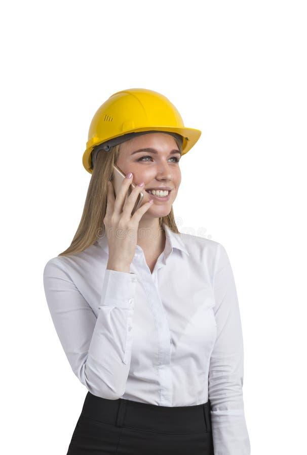 Isolerad stående av en affärskvinna som bär en gul hård hatt royaltyfri bild