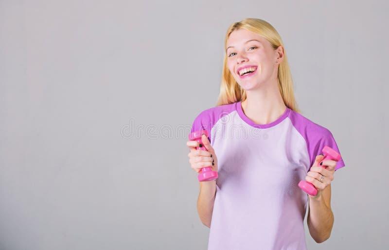 isolerad white f?r kondition instrukt?r sund livsstil f?r begrepp F?rtjusande blondin f?r kvinna som ?var med hanteln L?tta ?vnin royaltyfria foton
