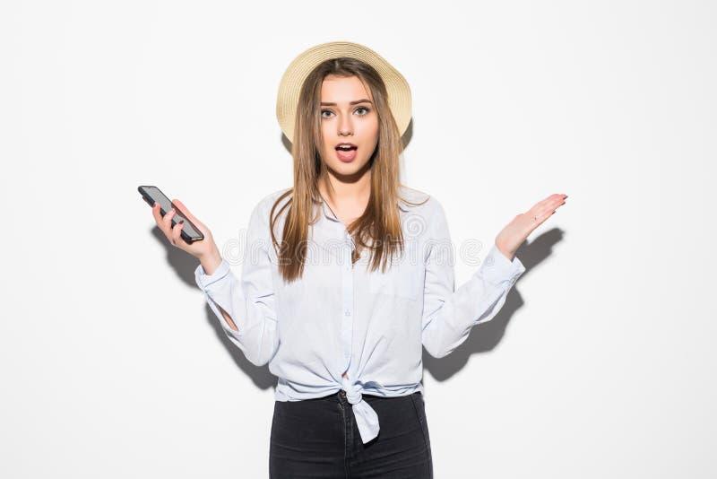 Isolerade den lyckliga upphetsade unga flickan för Closeupståenden i hatten som ser telefonen, vit bakgrund Positiva mänskliga si royaltyfri fotografi