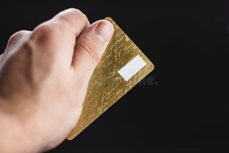 Isolerade den plast- kreditkorten för det manliga handinnehavmellanrumet eller affärskortet på svart studiobakgrund Bankrörelsese fotografering för bildbyråer