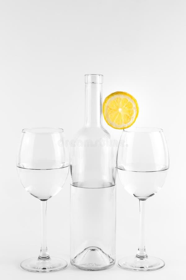 Isolerade flaska och exponeringsglas med citronen arkivfoton
