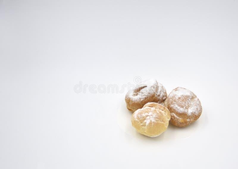 Isolerade mini- kakor och pusta med kräm- och sockerpulver royaltyfri foto