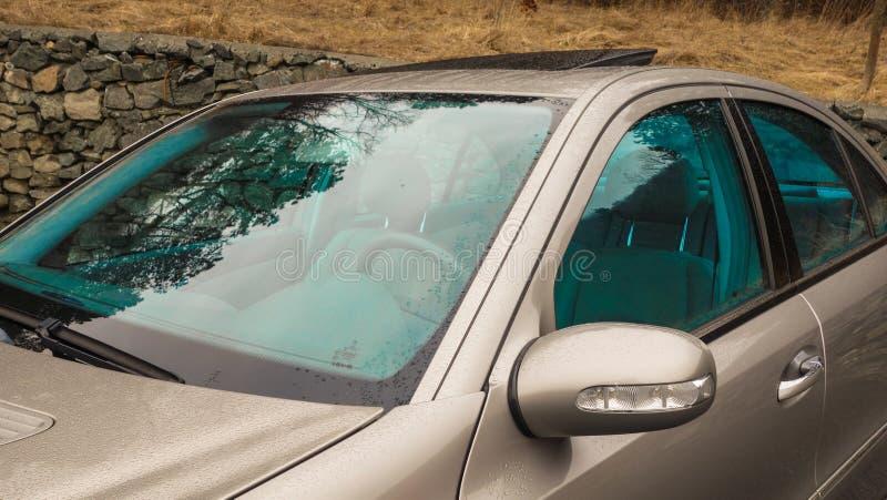 Isolerade/tonade fönster för blått och öppet soltak - tysk sedanbil i guld- metalliskt arkivbild