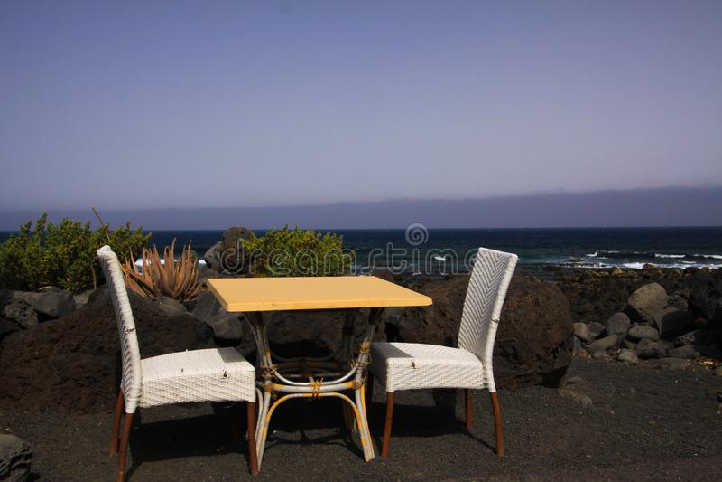 Isolerade två vita stolar och tabell på den svarta lavasandstranden med hav- och vågbakgrund - El Golfo, Lanzarote royaltyfri bild