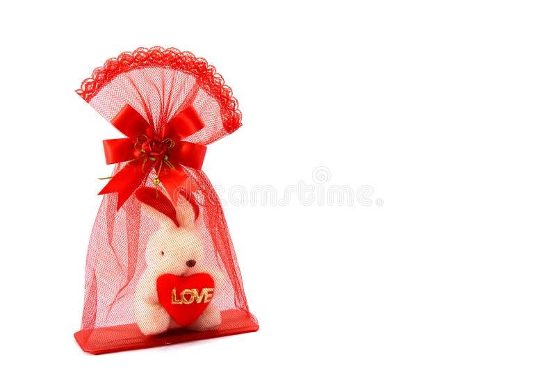 Isolerat av röd påse för ingrepp med liten vit kanin inom hållande hjärta- och förälskelsebokstav Stäng sig upp av kanindockan in arkivfoto