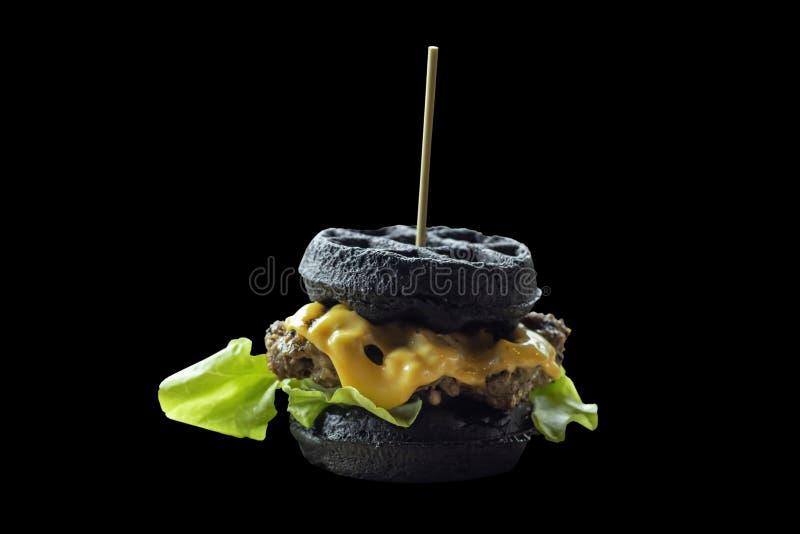 Isolerat hamburgaresvartgriskött på en svart bakgrund med clippin royaltyfri fotografi