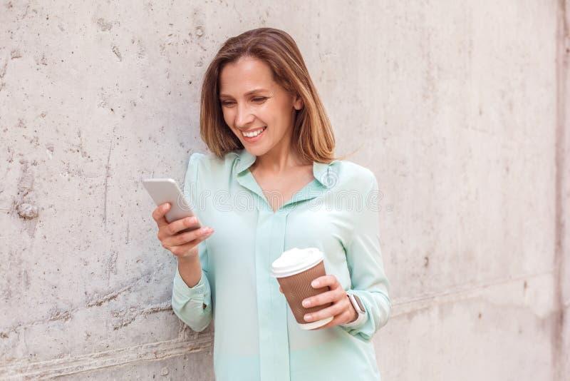 Isolerat luta för ung kvinna anseende på väggen som dricker kaffe som kontrollerar socialt massmedia på smartphonen arkivfoto