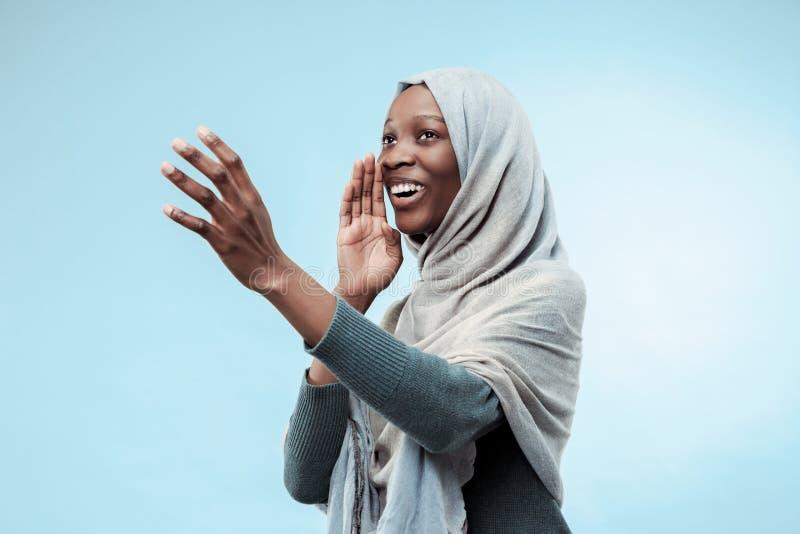 Isolerat på den blåa unga africasual kvinnan som ropar på studion royaltyfria foton