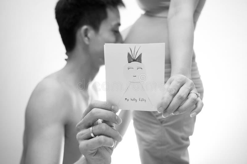 Isolerat på vitbakgrund par älskar älskvärt Kyssande buk för man av hans fru Att vänta på för mamma som och för farsa är nyfött,  royaltyfri bild