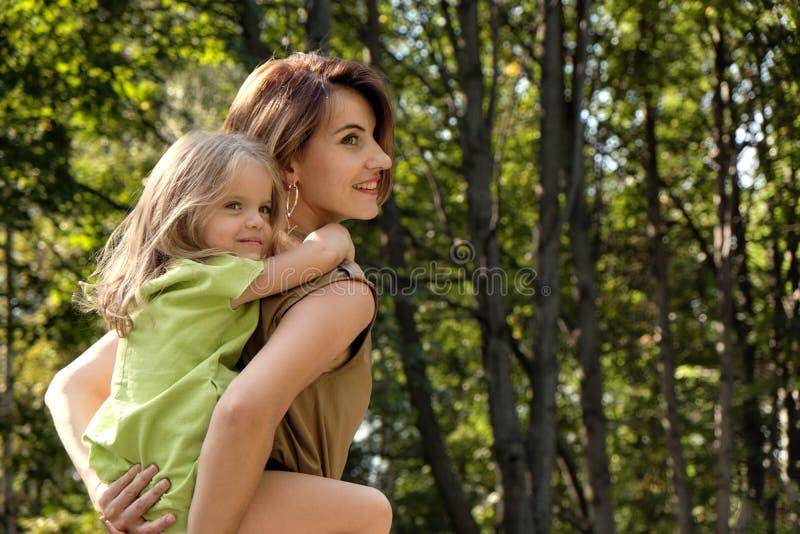 Isolerat p? vit bakgrund Den gulliga unga dottern som rider hennes mammas baksida, på naturen i, parkerar Begreppsmammadotter arkivfoton