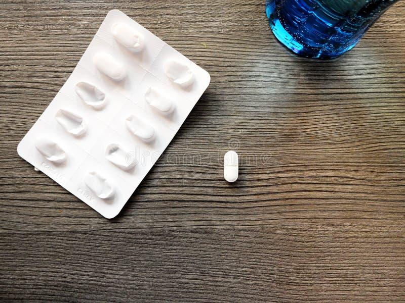 Isolerat piller bredvid packen av piller med ett exponeringsglas av vatten arkivbilder