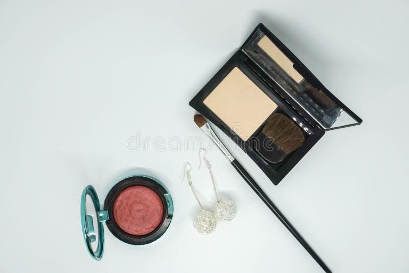 Isolerat skönhetsmedel, borste för ögonskugga och pulver i svart lyxigt fall och med örhängen för kvinnor royaltyfria foton
