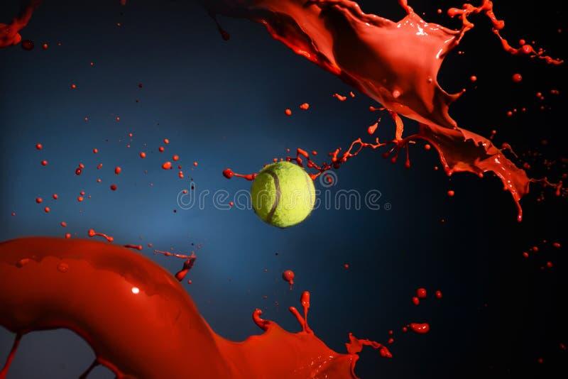 Isolerat skott av röd målarfärgfärgstänk och tennisbollen på blå bakgrund royaltyfri foto