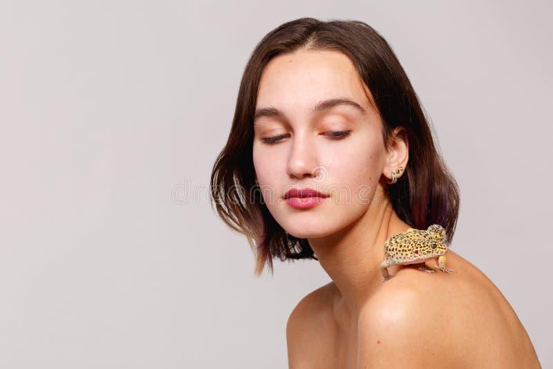 isolering En ung mörker-haired flicka med kort hår och kala skuldror På hennes skuldra är en leguangecko arkivfoto