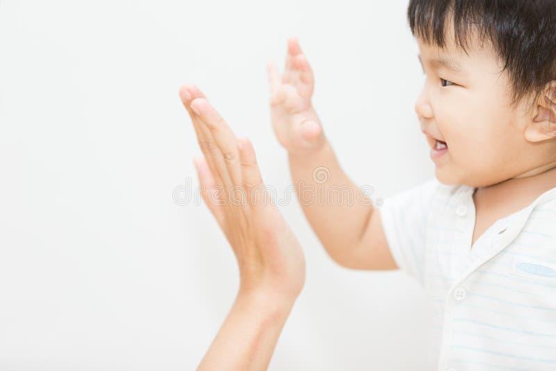 Isolez la main asiatique mignonne de contact de bébé avec la mère photographie stock libre de droits