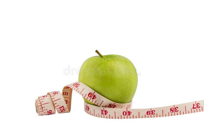 Isolez la pomme verte sur le bakcground blanc avec l'arou de mesure de bande photos stock