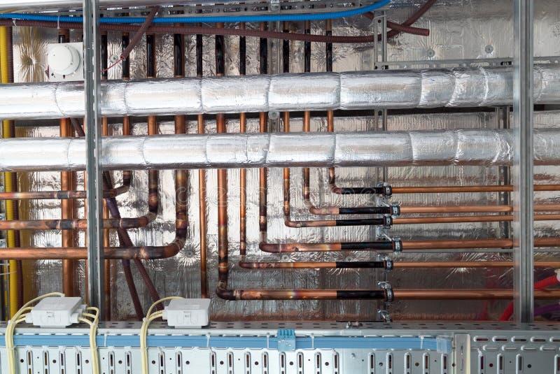 Isoliert Warmwasserleitungen und Kupferrohre hängen vom Subceiling lizenzfreie stockfotografie