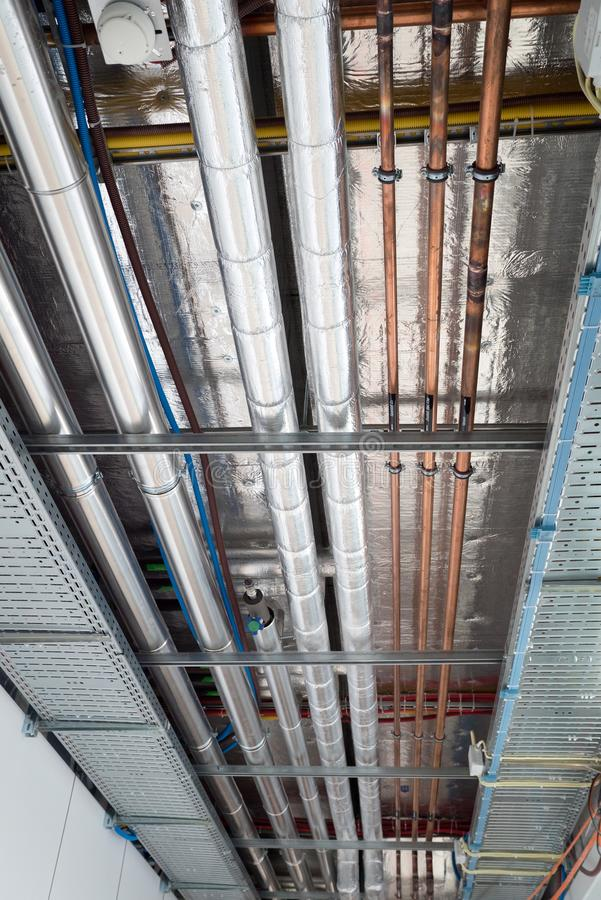 Isoliert Warmwasserleitungen und Kupferrohre h?ngen vom Subceiling lizenzfreies stockbild