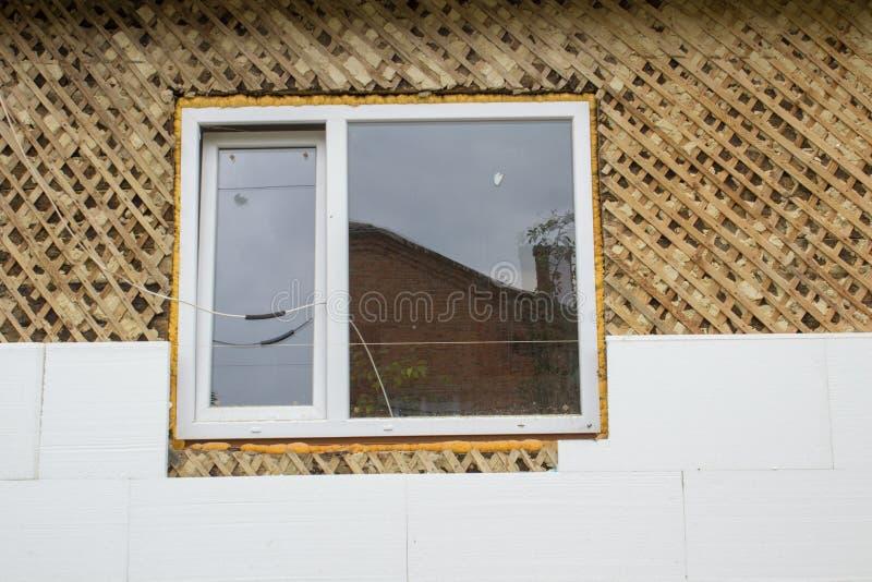 Isolierung der Fassade, isolieren das Holzhaus des Styroschaums von den Fenstern stockbild