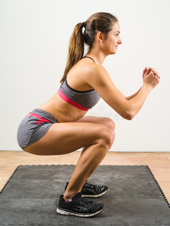Isometric squat. Photo of a young woman exercising and doing a isometric squat on a black floor mat stock photography