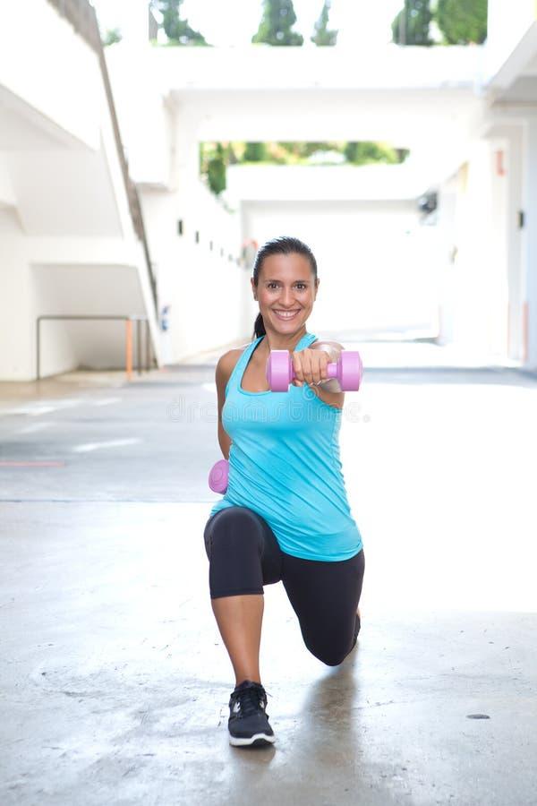 Ispanic-Sportfrau, die Laufleinen mit dem rosa Dummkopf zwei, im Freien tut stockfotografie