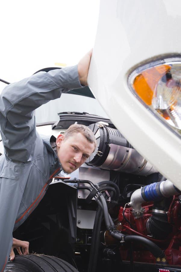 Ispettore che controlla motore funzionante sul grande camion bianco dei semi dell'impianto di perforazione immagini stock libere da diritti