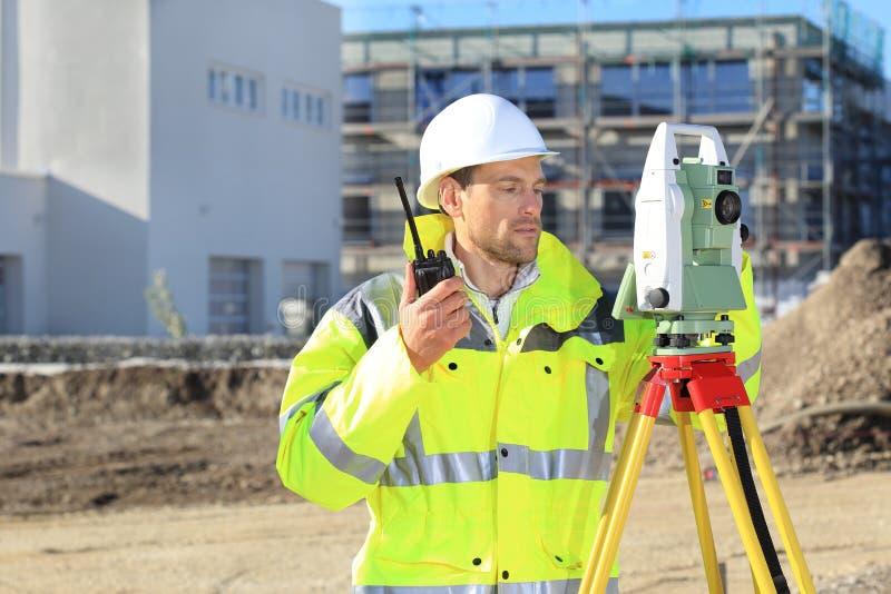 Ispettore con lo strumento di rilevamento topografico e radio davanti a nuovo buillding immagini stock