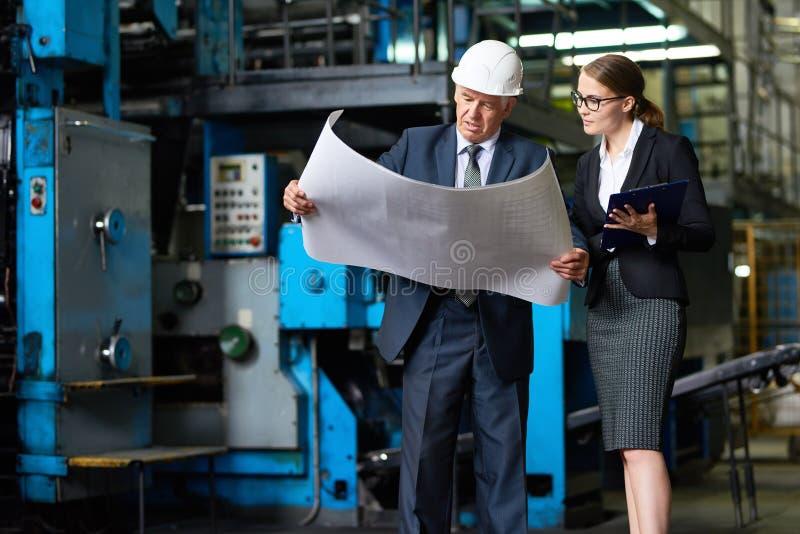 Ispettore senior che esamina i piani della fabbrica immagine stock libera da diritti
