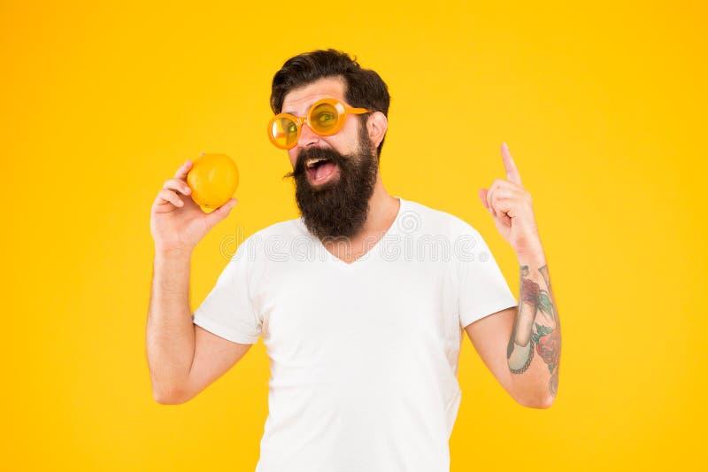 Ispirazione arancio del genio Uomo del genio con il dito indicante arancio su su fondo giallo I pantaloni a vita bassa barbuti ha immagini stock
