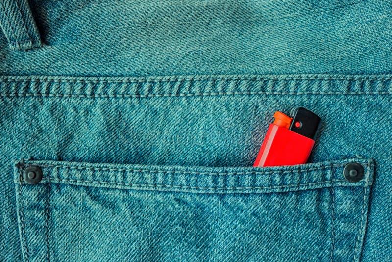 Isqueiro vermelho no bolso traseiro das calças de brim fotos de stock royalty free
